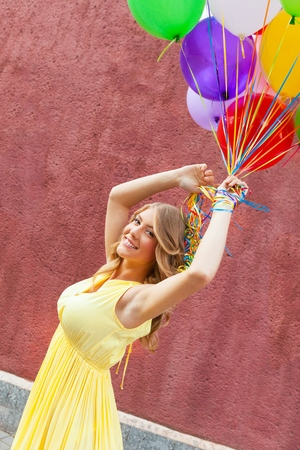 Sensual young woman big colorful latex balloons against the evening sun going down. Pastel colors. Outdoors, lifestyle