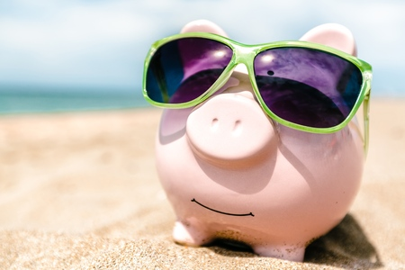 Summer piggy bank with sunglasses on the beach Stock Photo