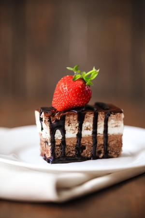 Piece of chocolate cake with icing and fresh berry on wooden background Фото со стока