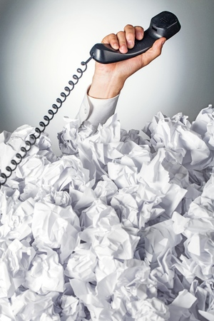 Hand with phone reaches out from big heap of crumpled papers