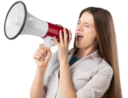 Young Businesswoman Shouting Through Megaphone isolated on white background Stock Photo