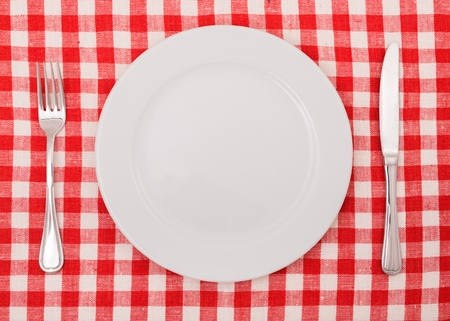 Table Setting with Plate, Fork and Knife on Checkered Table Cloth Stock Photo