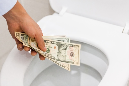Closeup of a Hand Putting Money in the Toilet