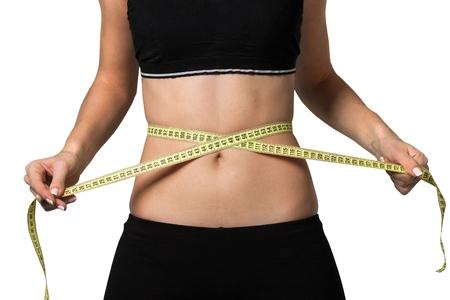 Female fitness model holding a tape measurer around her waist - weightloss concept