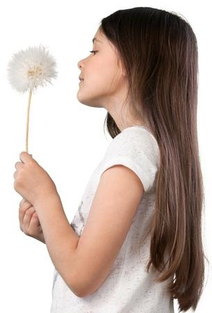 Cute Little Girl blowing dandelion on white background