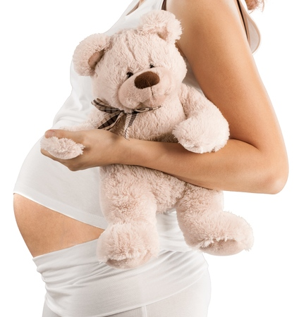 Pregnant woman holding teddy bear isolated on white background