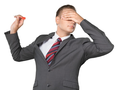 Portrait of a Businessman Throwing Dart with Hand over Eyes Stock Photo