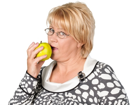 Mature Woman eating apple isolated on white background