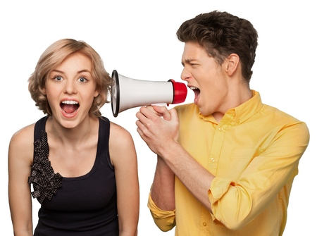 Angry young couple with megaphone isolated on white background Stock Photo