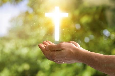 Femme avec croix blanche dans les mains priant pour la bénédiction de Dieu sur fond de lumière du soleil, concept d'espoir