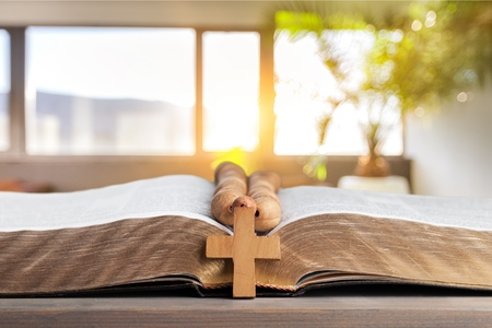 Rosary beads resting on open bible Stockfoto