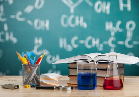 Classroom desk and drawn blackboard of chemistry