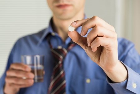 Close-up view photo of female hands holding one white round pill and glass of water. Young woman taking medication, feeling ill. Healthcare concept Фото со стока