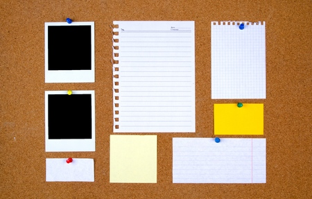Bulletin board with with blank notes and photographs
