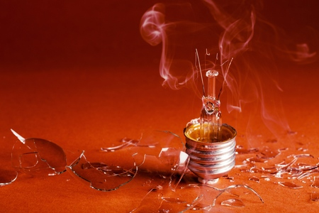 Burned Standard Incandescent Bulb with Smoke on Red Background Imagens