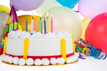 Decorative Birthday cake with candles and party favors Banque d'images - 106352557