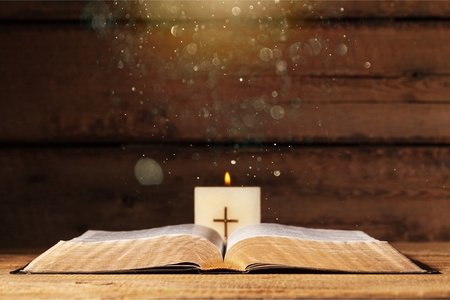 Burning candle and cross on wooden background