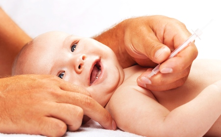 Doctor vaccinating baby isolated on a white