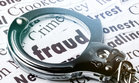 Handcuffs frame the word fraud among newspaper