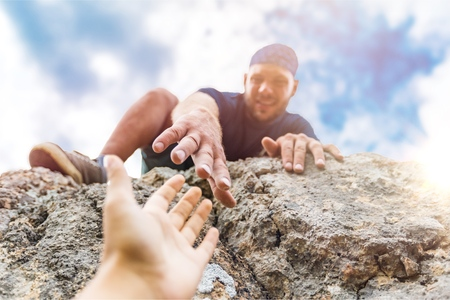Aventureros ayudándose unos a otros a escalar