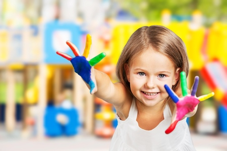 Little girl showing painted hands on background Фото со стока