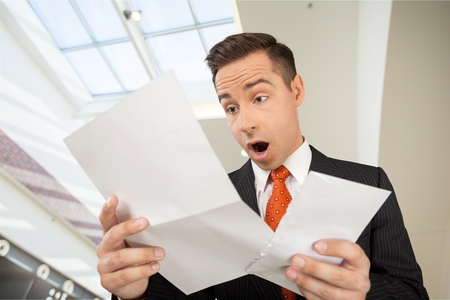 Man Opens Letter with Shocked Expression