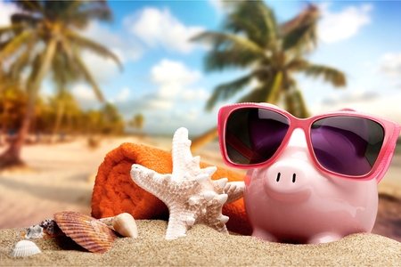 Piggy bank on sandy beach background