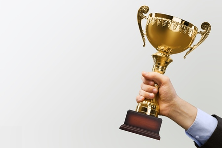 Close-up human hand holding golden Trophy on Stockfoto