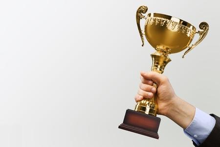 Close-up human hand holding golden Trophy on Foto de archivo