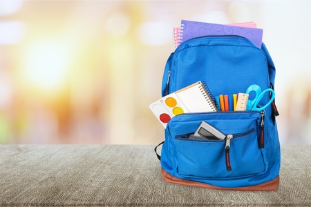 School bag on wooden background.
