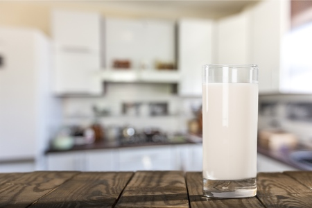 a glass of milk on the wooden table