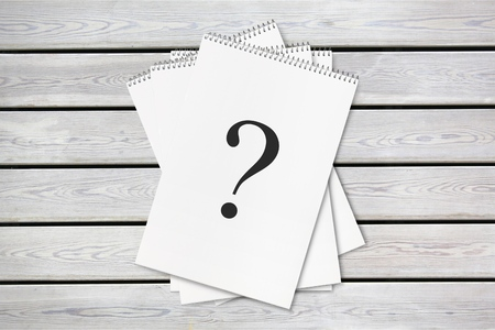 Question mark paper heap on wooden table Stock Photo