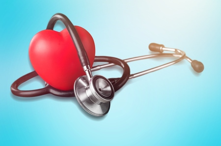 Stethoscope and small red heart on background Stock Photo