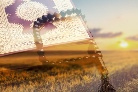 Islamic Holy Quran on field background Stock Photo