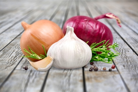 Onions isolated on wooden background