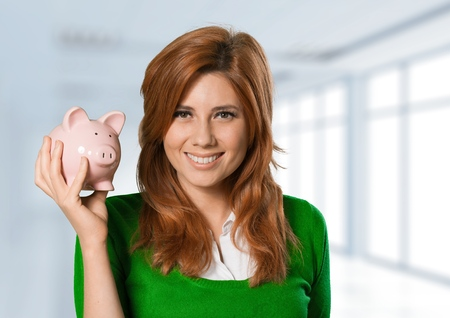 Close-up of young woman holding piggy bank against white background