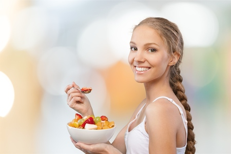 Smiling young woman having salad against white