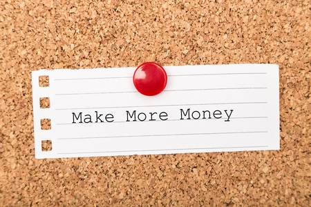 The phrase Make More Money typed on a piece of note paper and pinned to a cork notice board Stockfoto