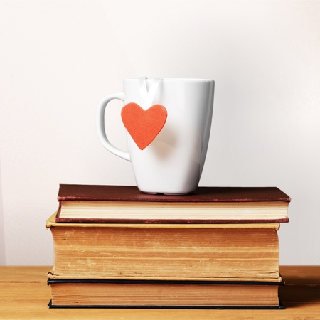 Coffee mug with heart shape on vintage books