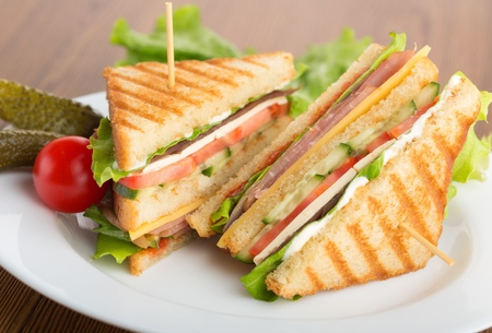 Photo of a club sandwich made with turkey, bacon, ham, tomato, cheese, lettuce, and garnished with a pickle and two cherry tomatoes. Stockfoto