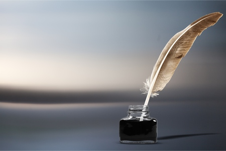 Quill pen with inkwell on wooden desk