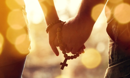 Couple praying together. Holding rosary in hand.