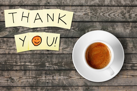 Coffee cup and thank you note   on wooden background