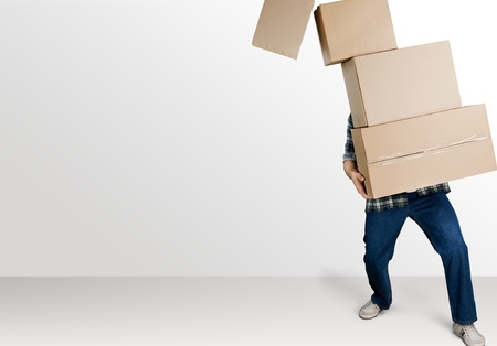 Delivery man carrying stacked boxes in front of face against white background