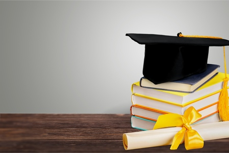 Graduation mortarboard on top of stack of books on white background