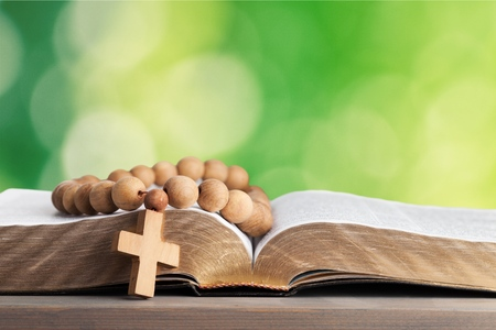 Rosary beads resting on open bible on wooden table