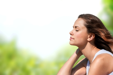 Calm beautiful smiling young woman with ponytail enjoying fresh air outdoor, relaxing with eyes closed, feeling alive, breathing, dreaming. Copy space, green park nature background. Side view portrait Banque d'images