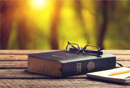 Holy bible with eye glasses and note book, pencil   on wooden table with window light in the morning, copy space