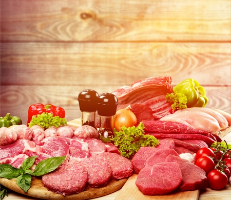 Fresh raw meat with vegetables on brown wooden table at wooden background Stock fotó