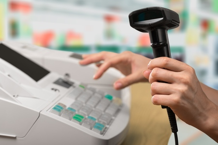 Caisse enregistreuse avec écran LCD et main des travailleurs tenant le papier de réception sur l'intérieur du supermarché floue Banque d'images